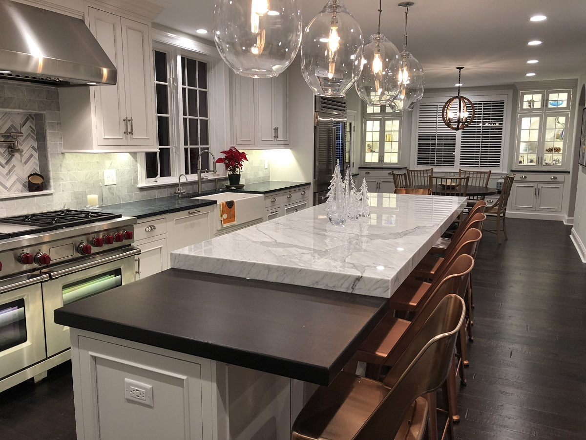 Kitchen with white cabinets, an island, and dark wood floors.