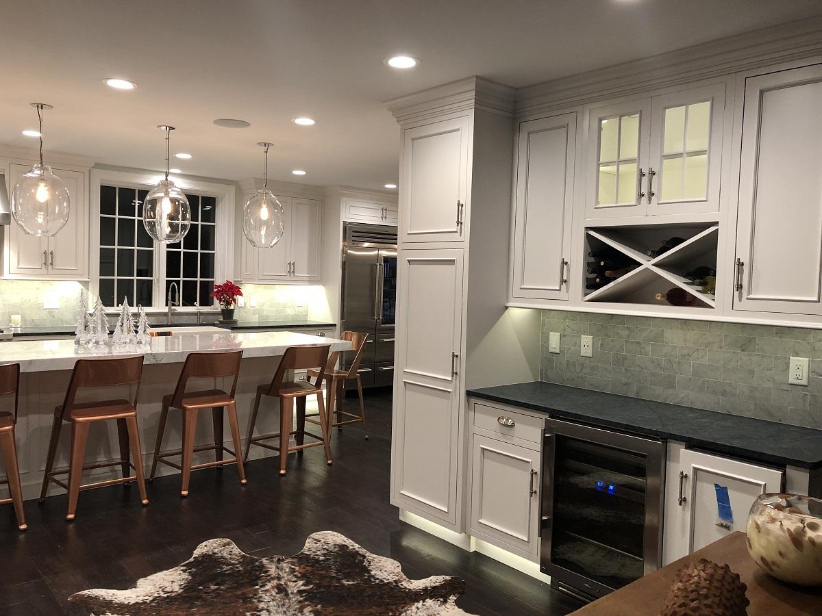 Large white kitchen with island seating and wine fridge
