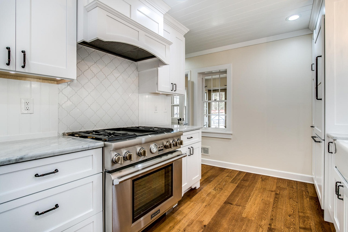 White farmhouse kitchen with wood floors, oven, and range